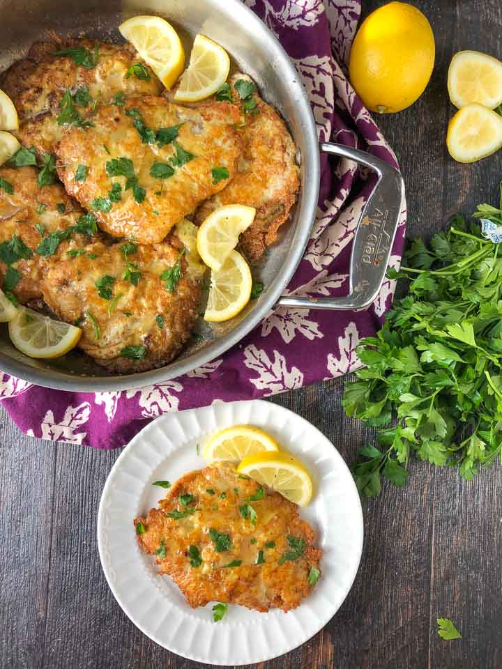 white plate and pan with low carb pork chops Romano with lemon wedges and a bunch of fresh parsley and lemons