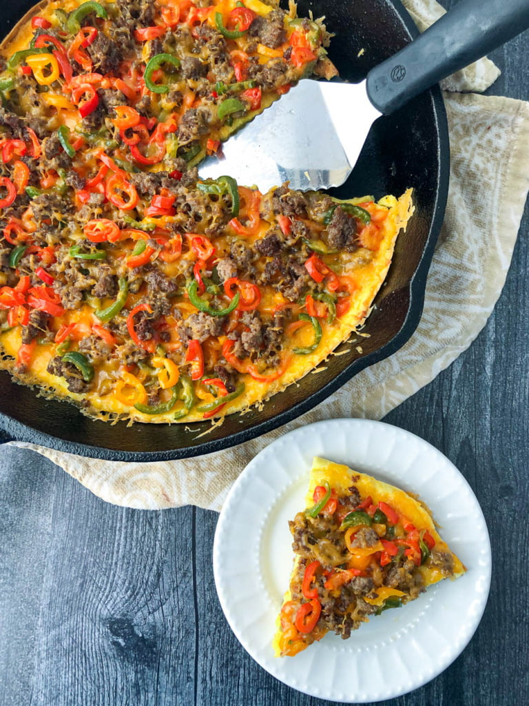 aerial view of a skillet and white plate with low carb breakfast pizza and a silver spatula