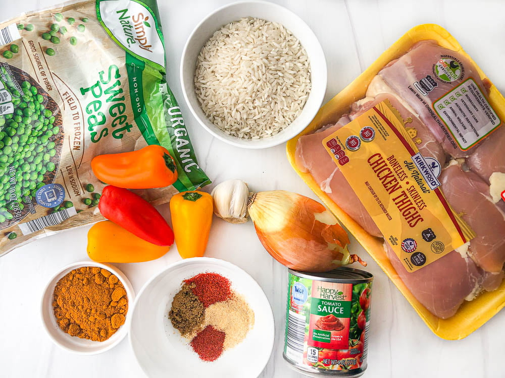 ingredients to make this recipe: chicken thighs, frozen peas, white rice, peppers, onions, garlic, a can of tomato sauce and spices
