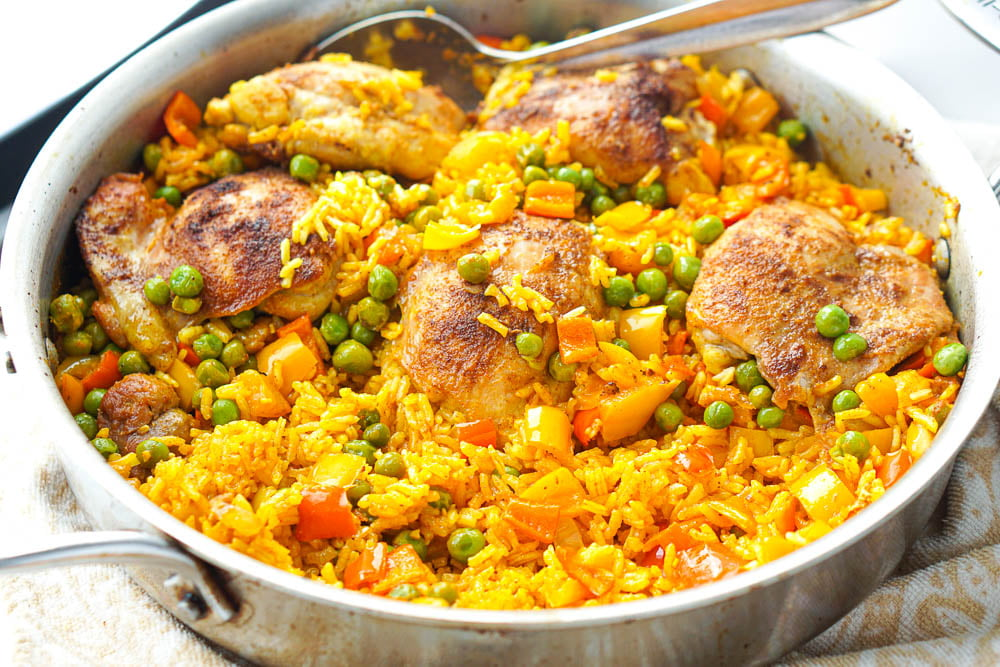 a silver pan with chicken thighs and yellow rice with peppers and peas
