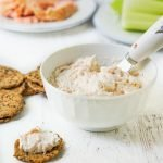 white bowl with low carb smoked salmon cream cheese dip, celery, crackers and text overlay