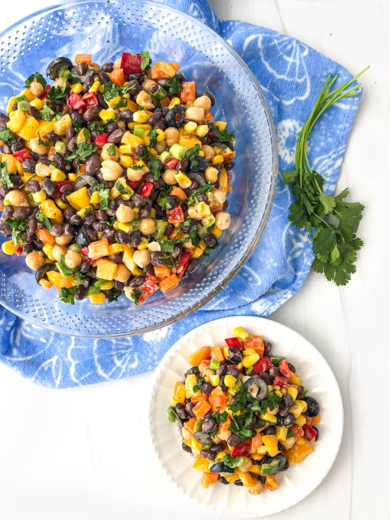 aerial view of a bowl and plate of veggie and bean salad and a sprig of cilantro
