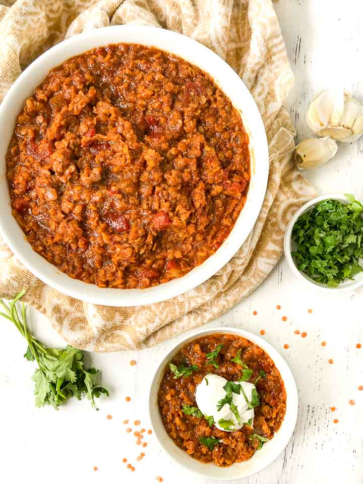 large and small white bowl with spicy Mexican red lentils chili and a bowl of and sprig of fresh cilantro