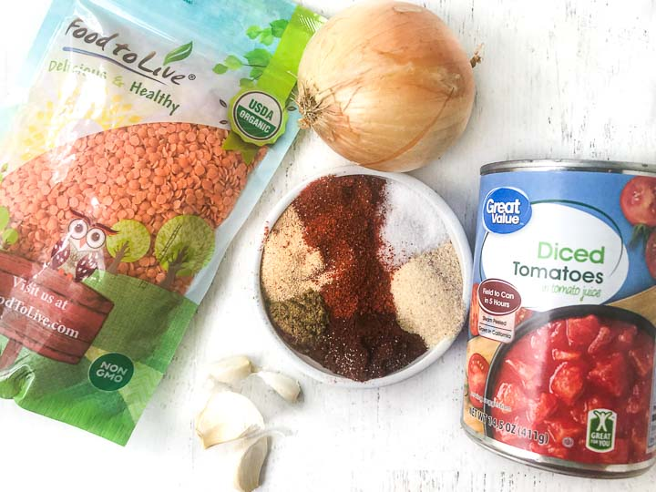 ingredients for this vegetarian lentils: bag red lentils, raw onion, can of diced tomatoes, garlic cloves, bowl of spices.