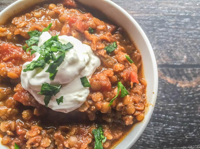 closeup of cooked red lentils with sour cream and cilantro