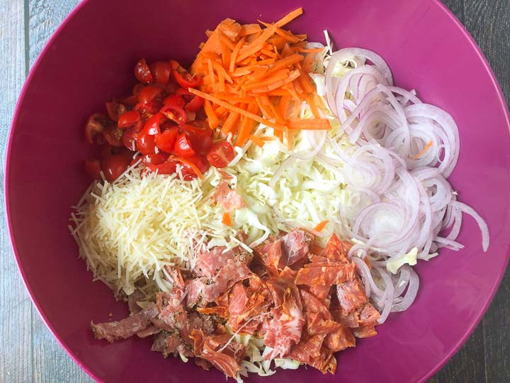 big magenta bowl with chopped ingredients for antipasto cabbage salad