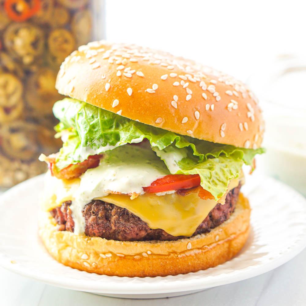 loaded burger with dripping jalapeno aioli burger sauce and sesame bun