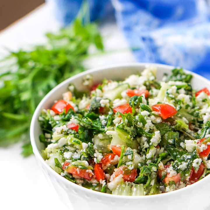 close up of gluten free cauliflower rice tabouli salad with parsley springs in background