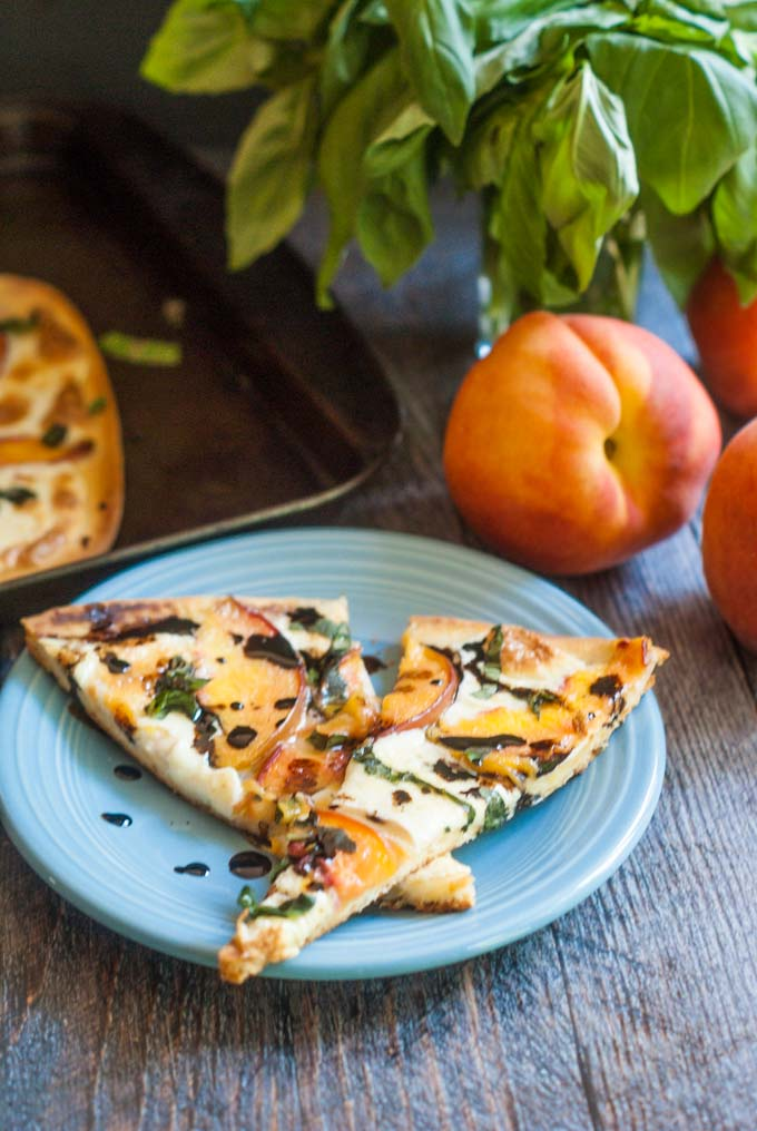 blue plate with peach & basil flatbread pizza and a balsamic reduction with a bunch of fresh basil and peaches