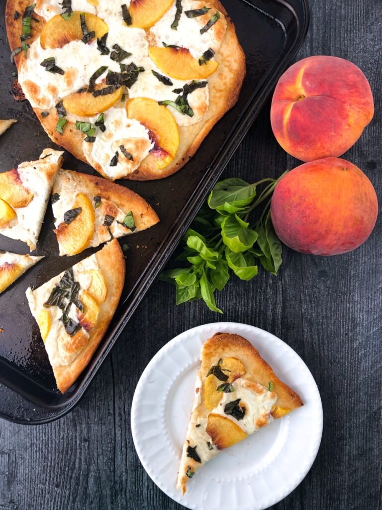 aerial view of a black pan with naan flatbread pizzas with peaches and mozzarella cheese, fresh basil and fresh peaches