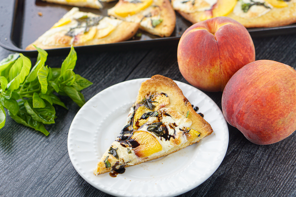 closeup of a piece of peach flatbread with balsamic vinegar glaze and fresh peaches and basil in the background