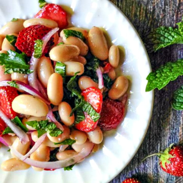 white plate with strawberry and mint bean salad
