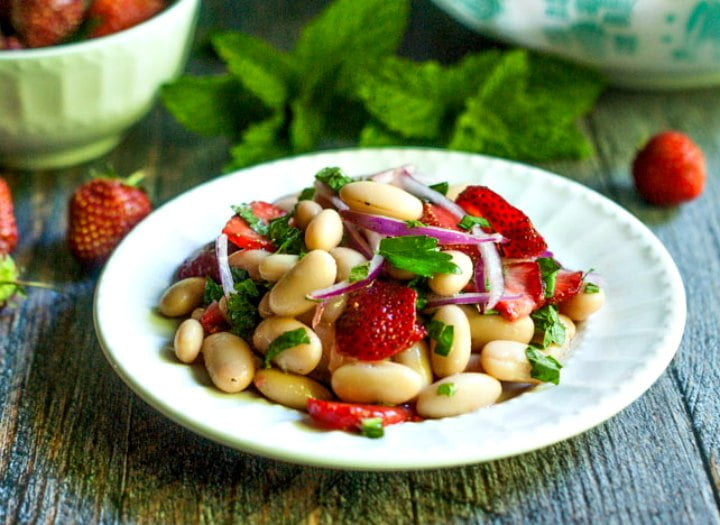 white plate with a serving of bean salad with fresh mint and strawberries in the background