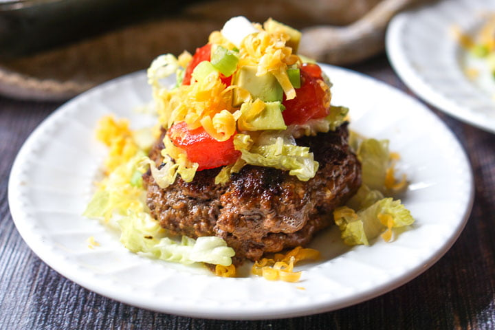 white plate with keto cheddar stuffed taco burger