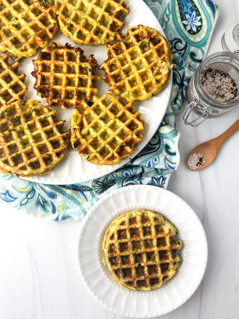 aerial view of large and small white plates with low carb veggie waffles and a jar of salt
