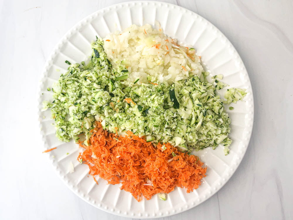 white plate with grated raw carrots, onions and zucchini