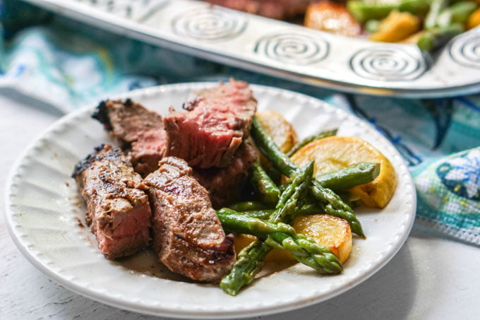 white plate wit pieces of flank steak, asparagus and yellow zucchini