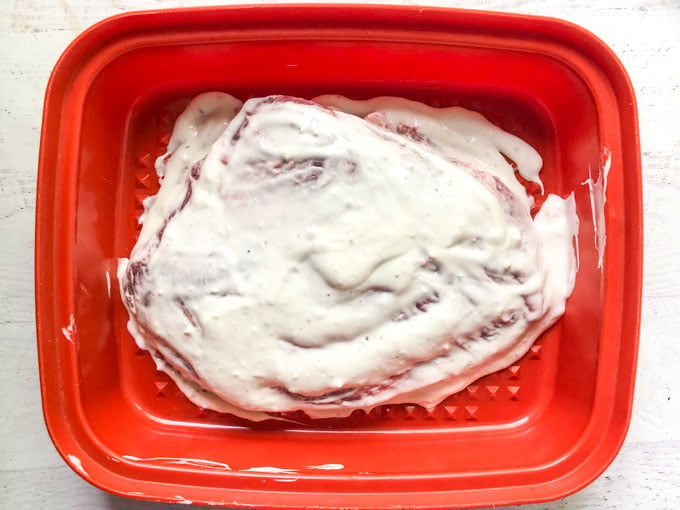 blue cheese marinated flanks steak in red container