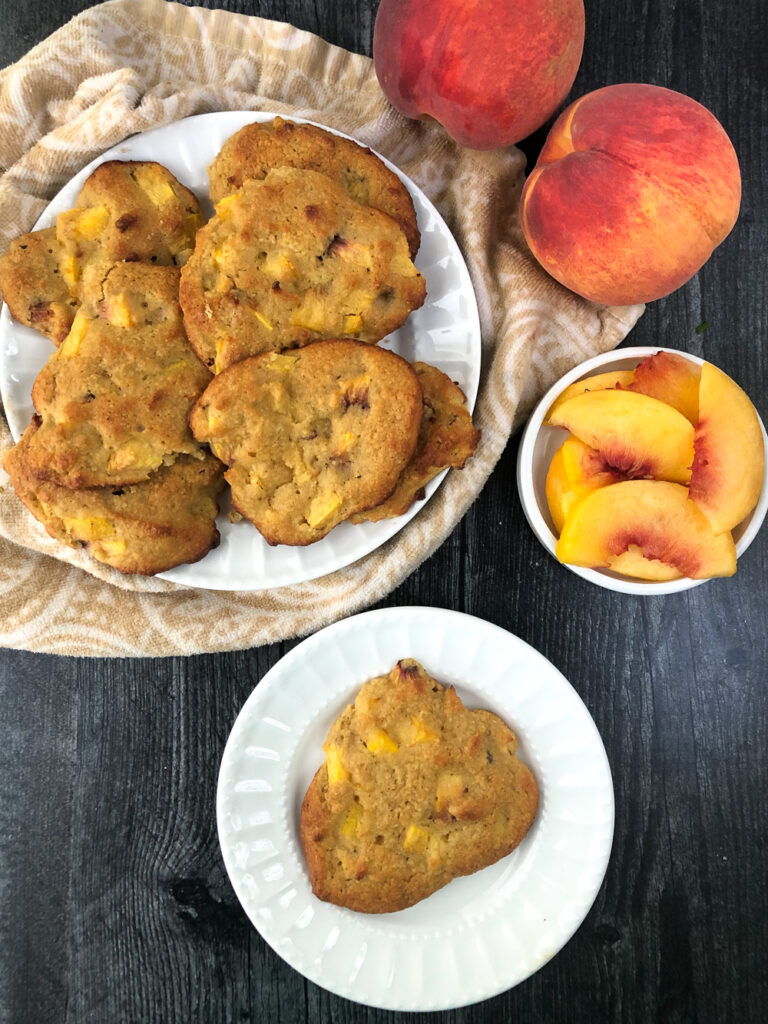 aerial view of 2 white plates with peach scones and some sliced and whole fresh peaches