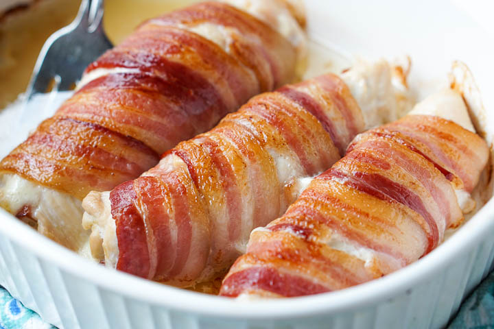 white baking dish with keto bacon wrapped chicken cordon bleu with a fork