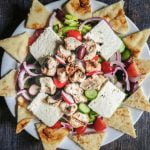This easy Greek chicken salad is filled with tasty Mediterranean goodies and topped with chicken kebabs. Serve with pita bread for a light but tasty dinner.
