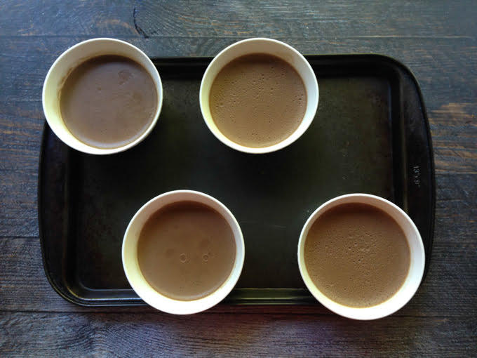 A photo of 4 white bowls filled with chocolate panna cotta - aerial view.