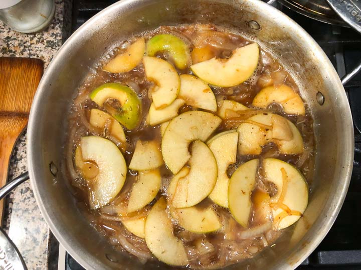 pan on the stove with sautéed apples and onions