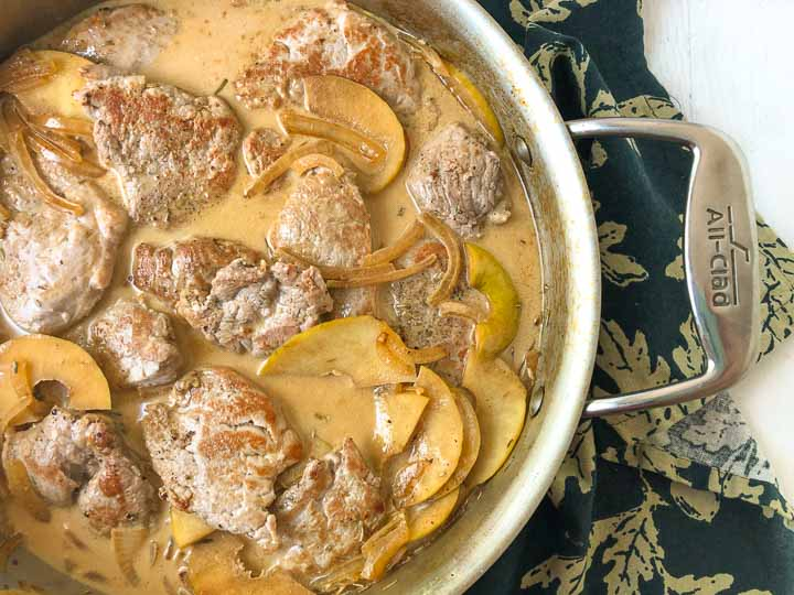 closeup of pan with creamy pork tenderloin and apples on dark greek floral tea towel