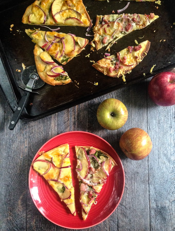 apple and cheese flatbreads on naan bread on a cookie sheet, apples and red plate with a few slices on it