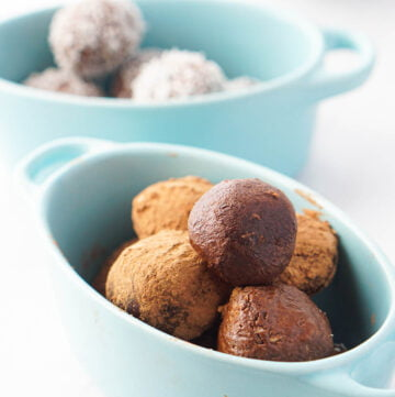 blue bowls with keto protein balls which are chocolate coconut flavored