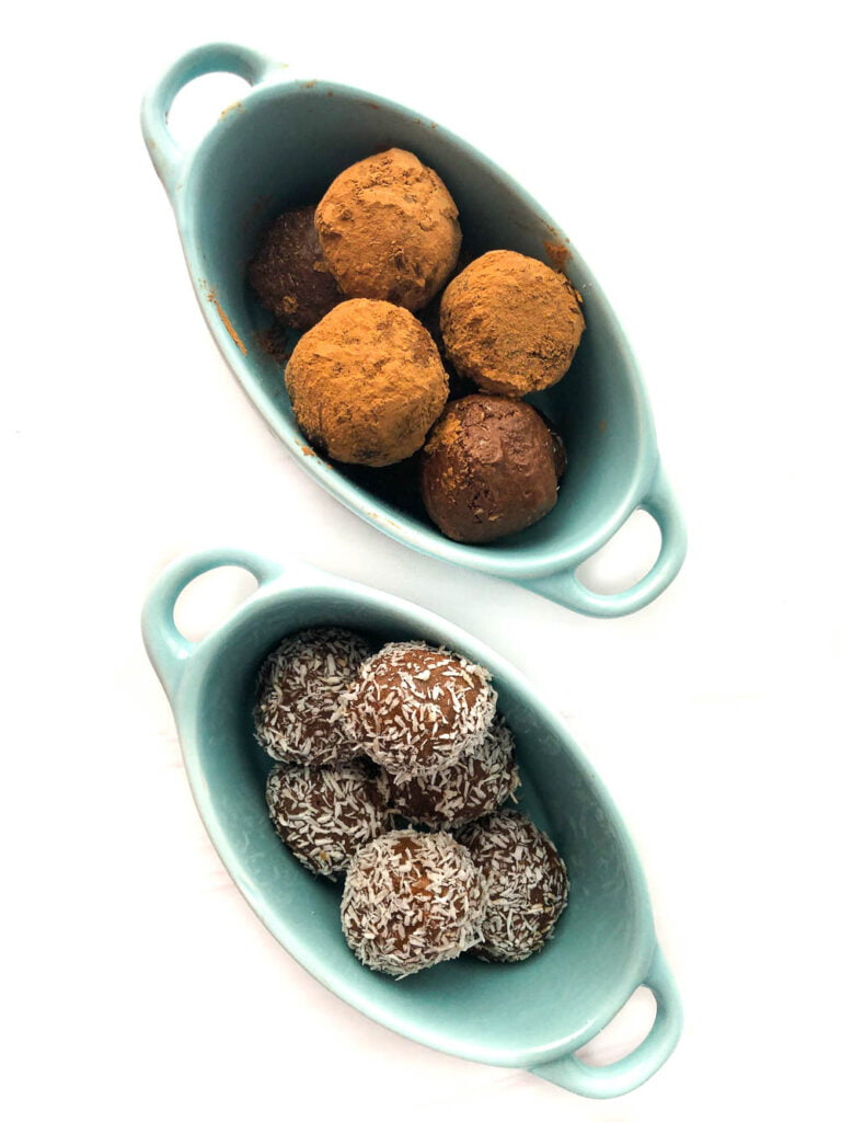aerial view of two blue bowls - one with cocoa covered energy bites and the other with coconut covered protein balls