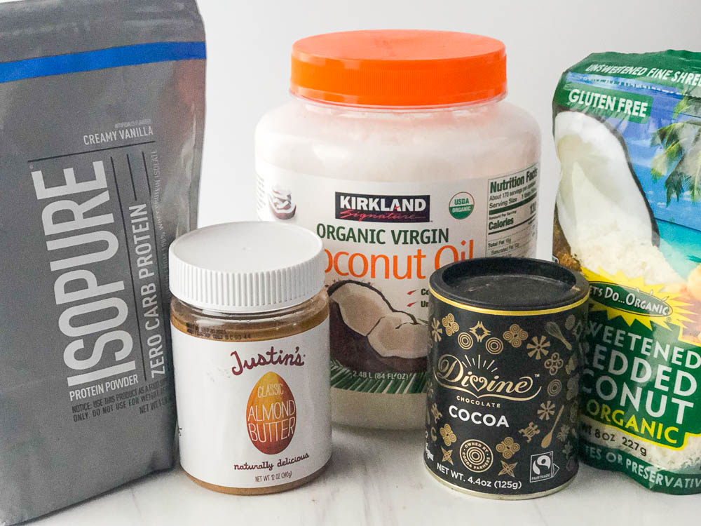 5 ingredients for protein bites - Isopure protein powder, coconut oil, Justins almond butter, Divine cocoa and shredded coconut