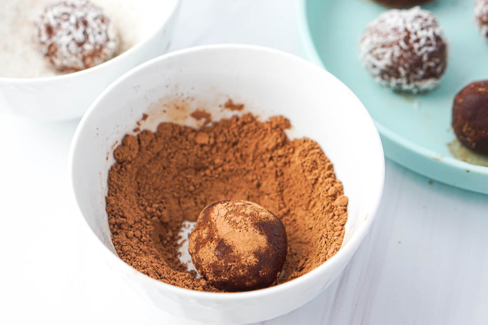 white bowl with cocoa powder and a protein ball half rolled