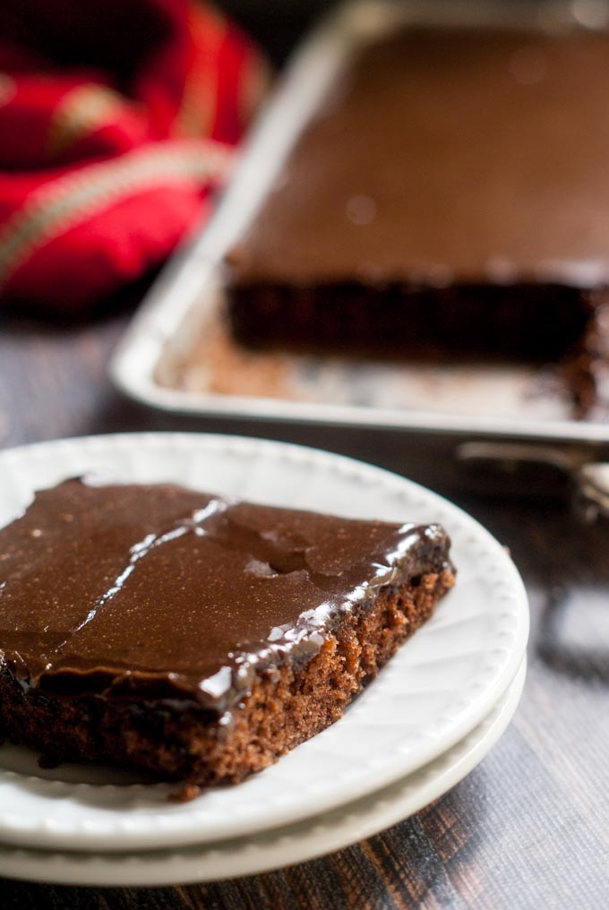 slice of chocolate cake on plates with a cookie sheet in the background and red tea towel