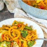 skillet with Thai butternut squash noodles and vegetables and white plate with text overlay
