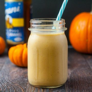 mason jar of low carb salted caramel pumpkin smoothie with blue straw, pumpkins and Torani bottle