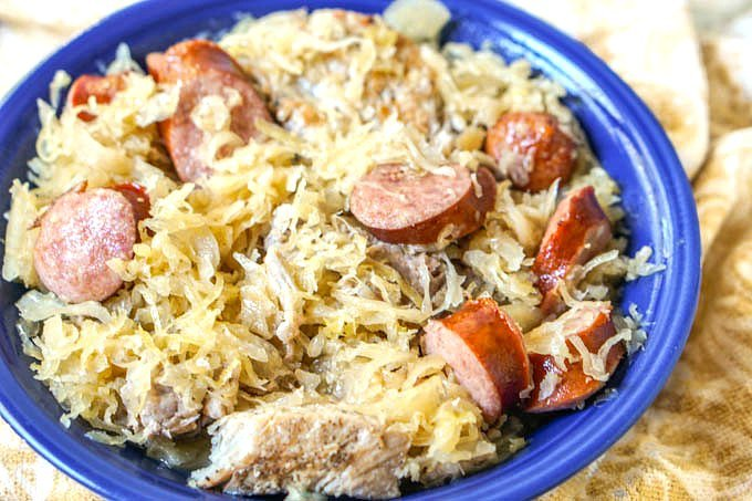 big blue bowl of New Year's pork, sauerkraut and kielbasa Instant Pot recipe