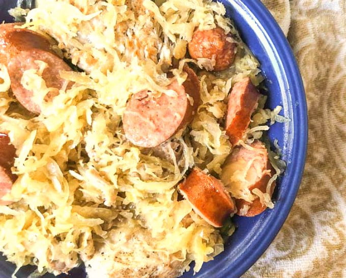 blue bowl with Instant Pot pork and sauerkraut with kielbasa