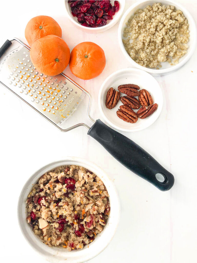 aerial view of a bowl of quinoa with a zester, raw oranges, cooked quinoa and raw pecans