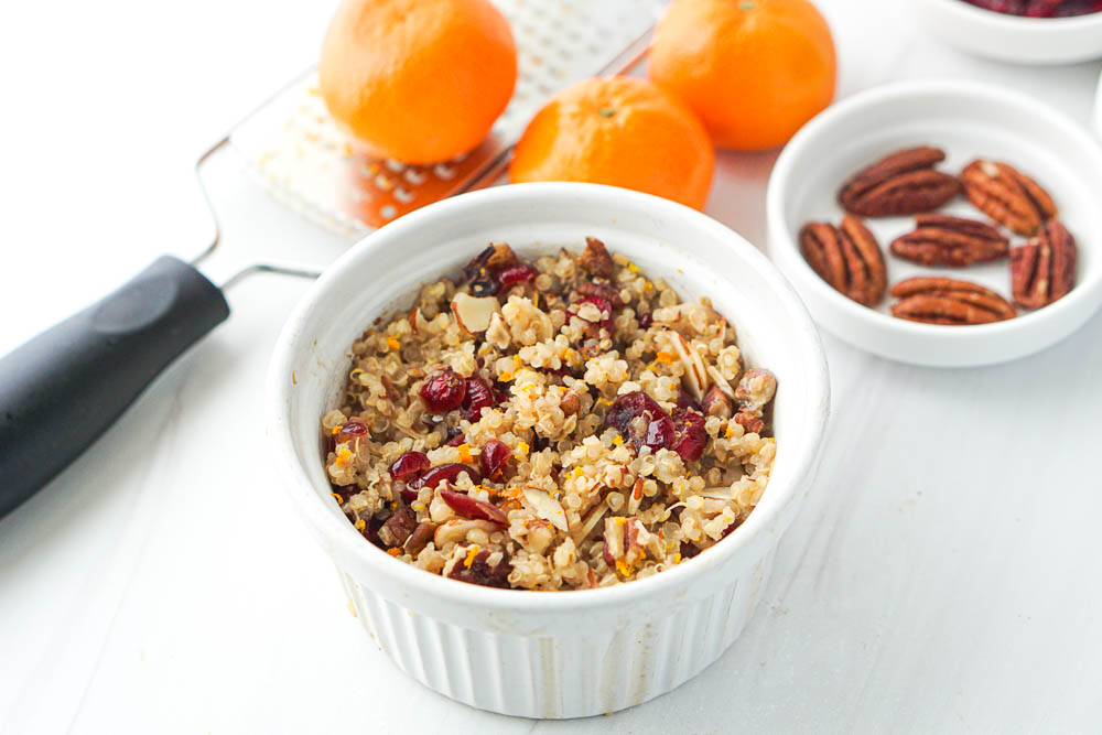 ramekin of hot quinoa with cranberries and fresh oranges & pecans in the background