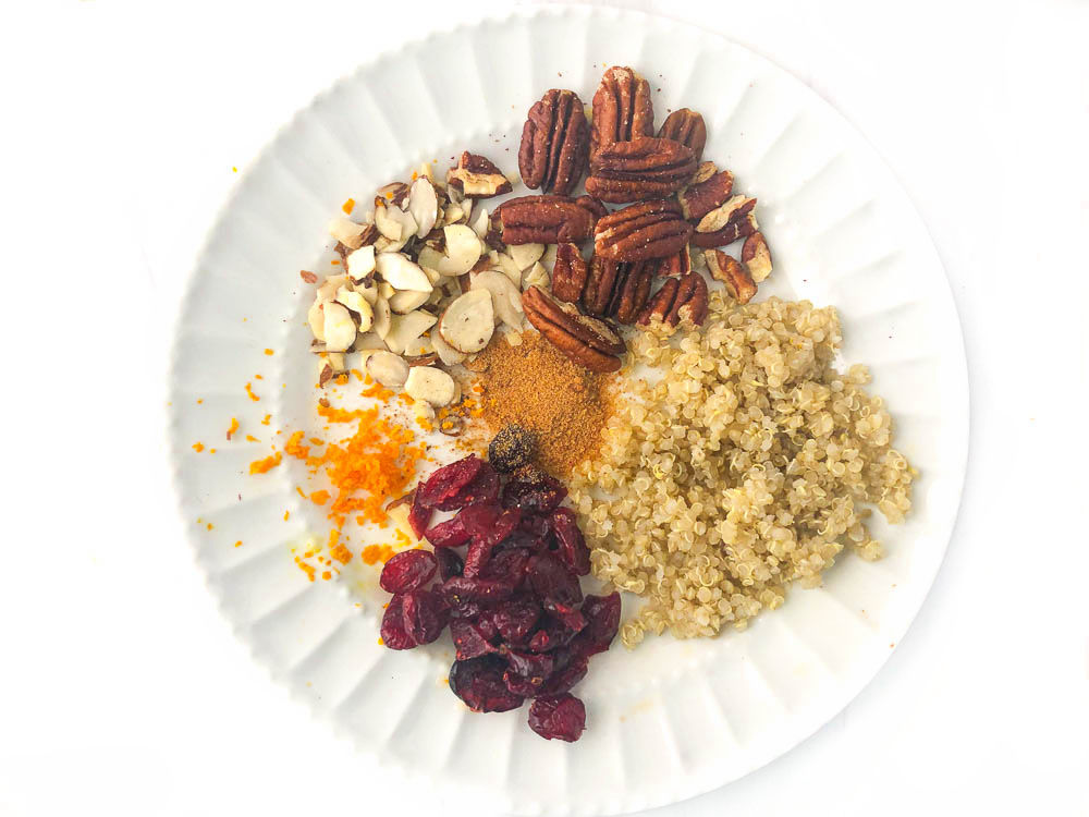 ingredients for this recipe on white plate - raw pecans, almond slices, coconut sugar, orange zest, cooked quinoa and dried cranberries