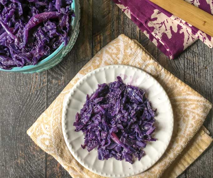 white plate with purple cooked cabbage on beige tea towel