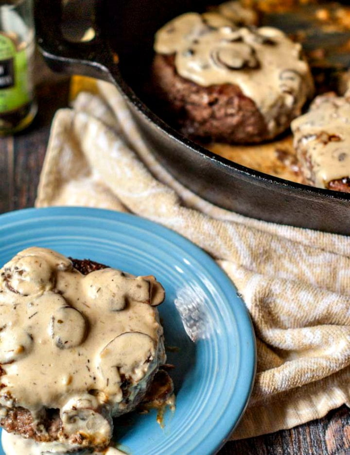 blue plate with a burger with creamy mushroom sauce and skillet in the background