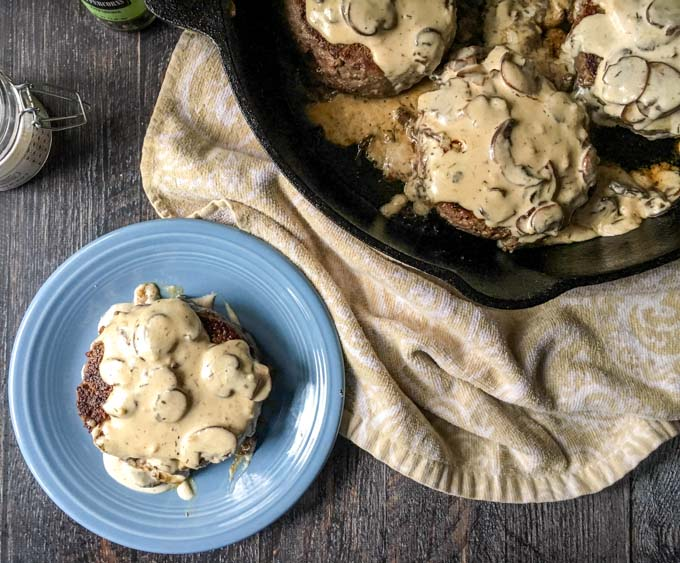 blue plate and cast iron skillet with creamy mushroom burgers