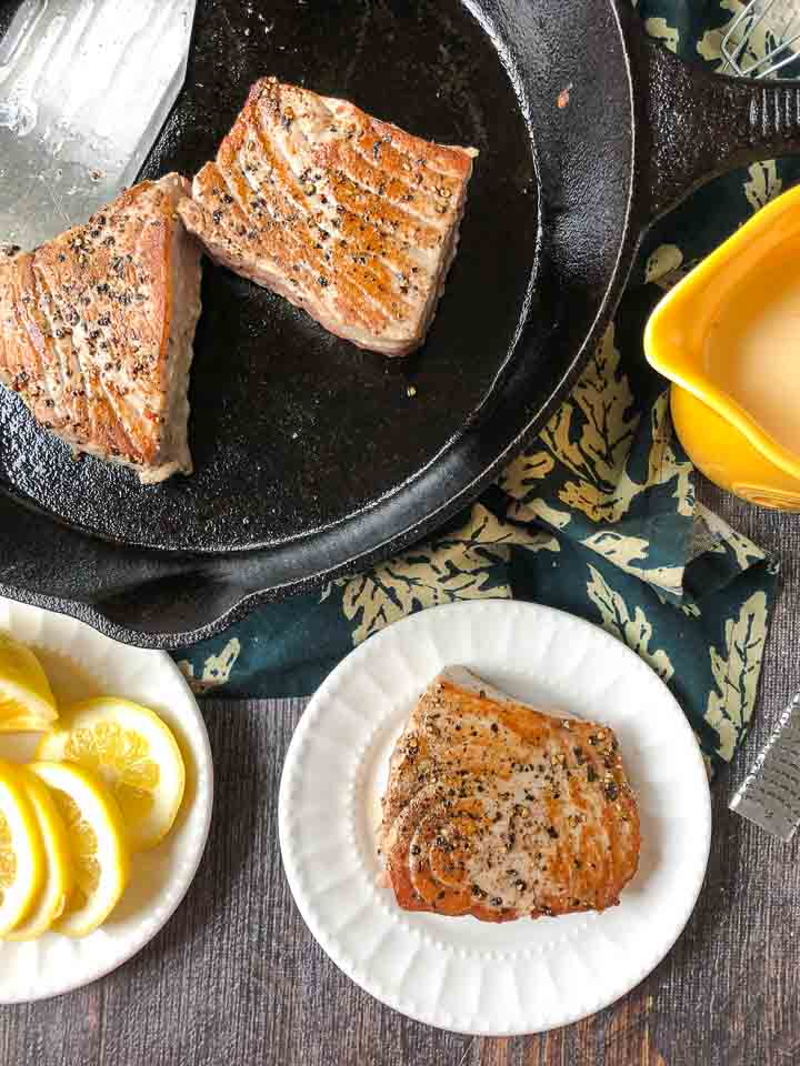 cast iron skillet and a white plate with pepper tuna steaks, sliced lemon on a plate and yellow pitcher with lemon dijon sauce