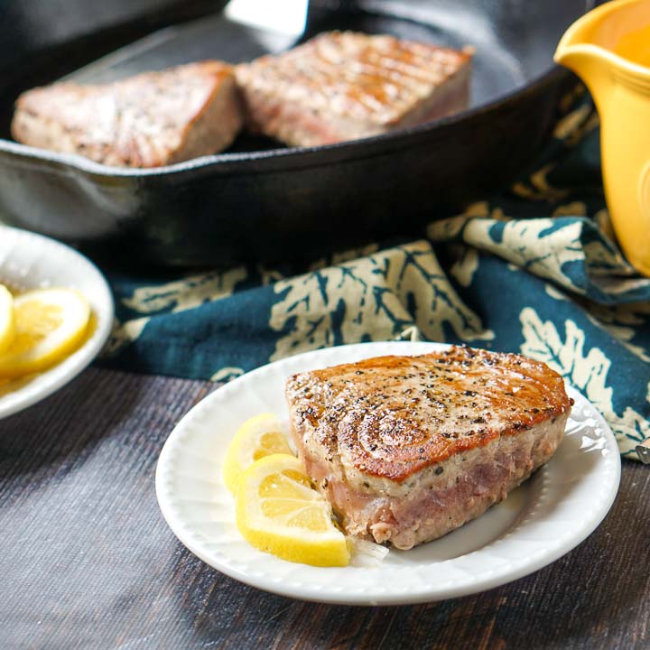 white plate with pepper tuna steak, lemon slices and cast iron skillet in the background
