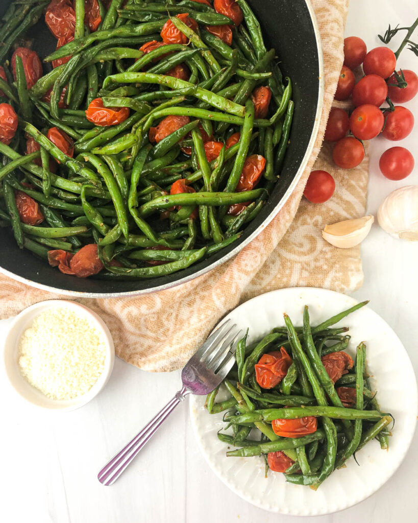 pan and white dish with grape tomatoes and green beans side dish and fresh cherry tomatoes, garlic and parmesan cheese