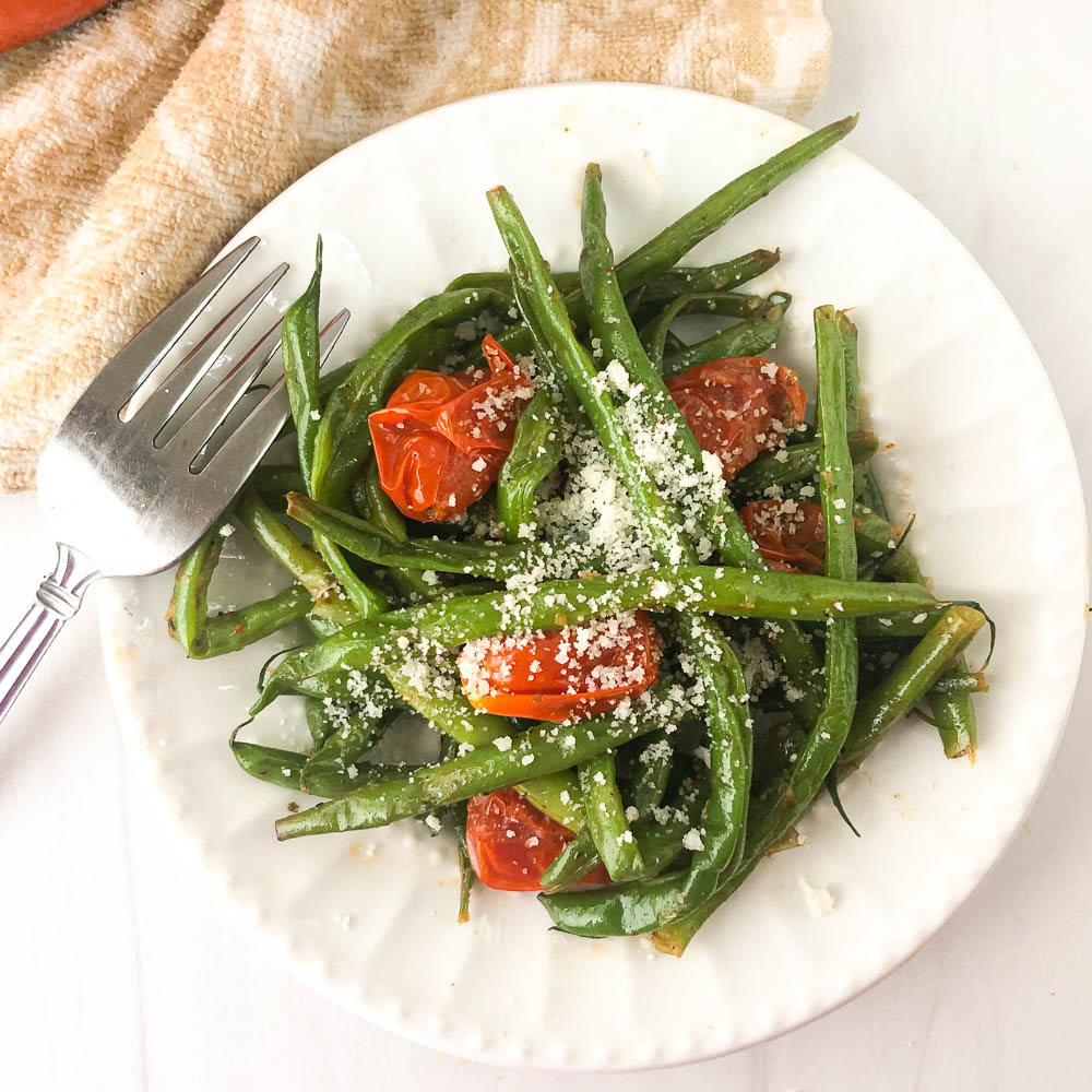 white plate with green beans and tomatoes side dish and a fork