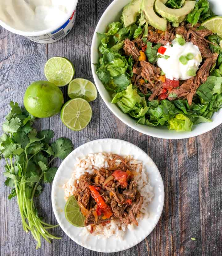 big salad bowl with barbacoa beef and a plate with rice and beef also fresh cilantro and limes