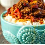 Closeup of Barbacoa beef on rice in blue bowl.